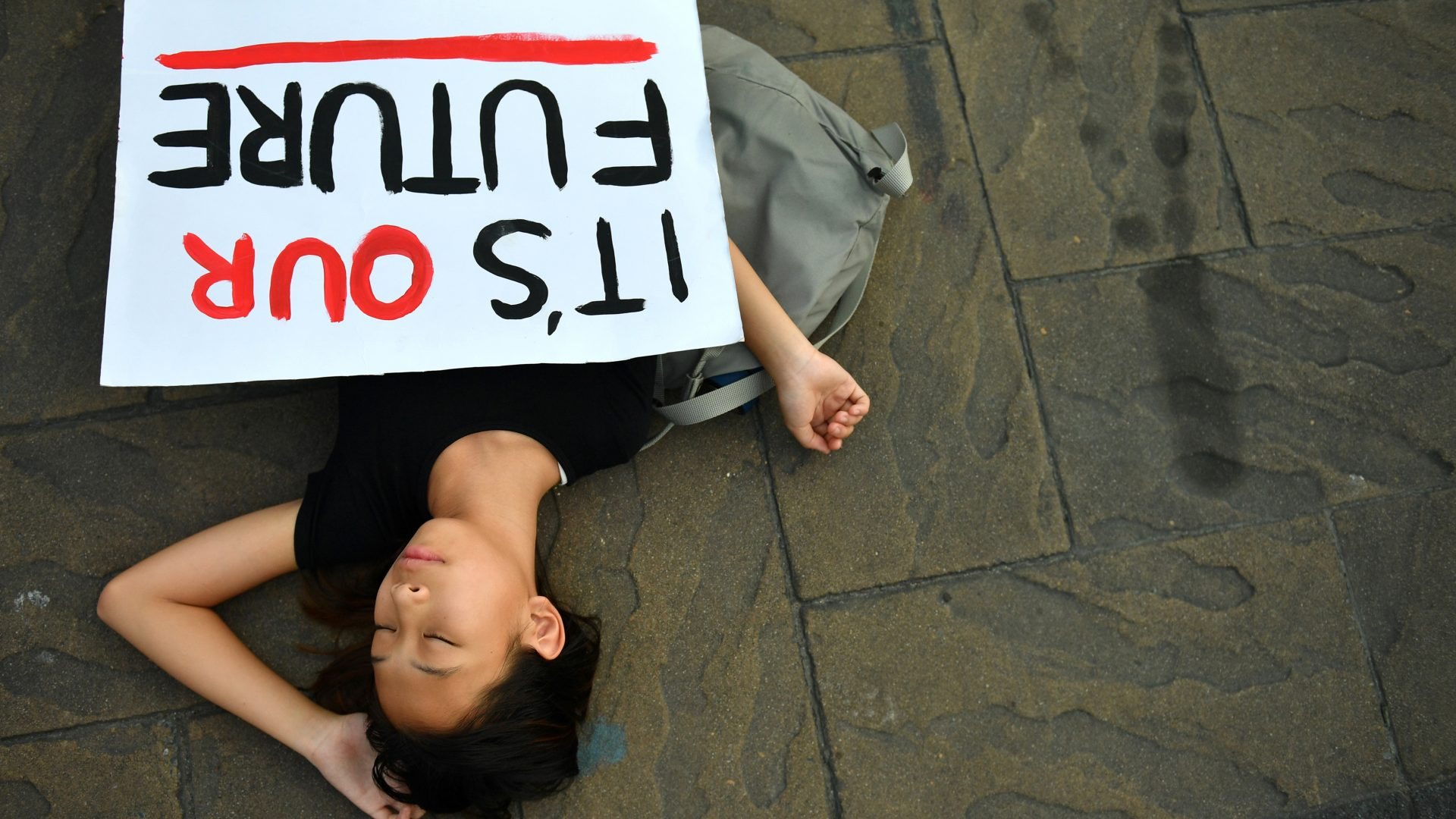 A climate change activist lies on the ground as she stages a 'drop dead' flashmob protest against climate change consequences at Lumpini Park in Bangkok, Thailand